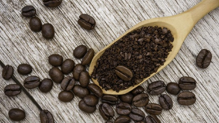 Closeup instant granulated coffee in wooden scoop with roasted coffee bean isolated on old rustic wood table  background. Top view. Flat lay.