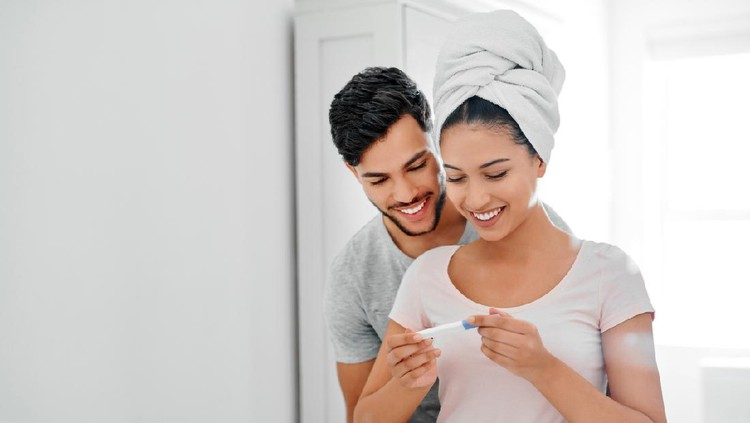 Shot of a happy young couple looking at their pregnancy test results in the bathroom at home