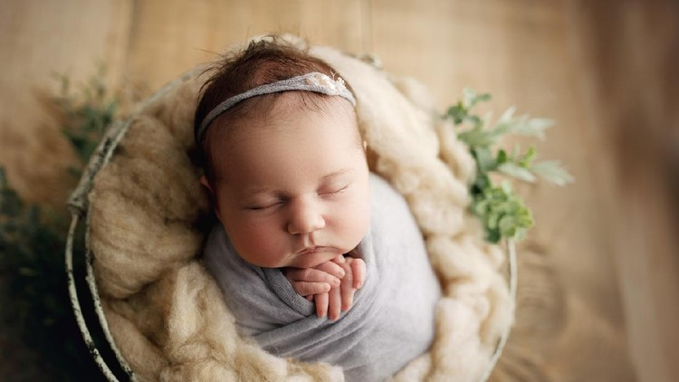 20 day old baby girl with chunky cheeks, swaddled in pale purple with a matching headband, in a prop basket for her newborn milestone photos