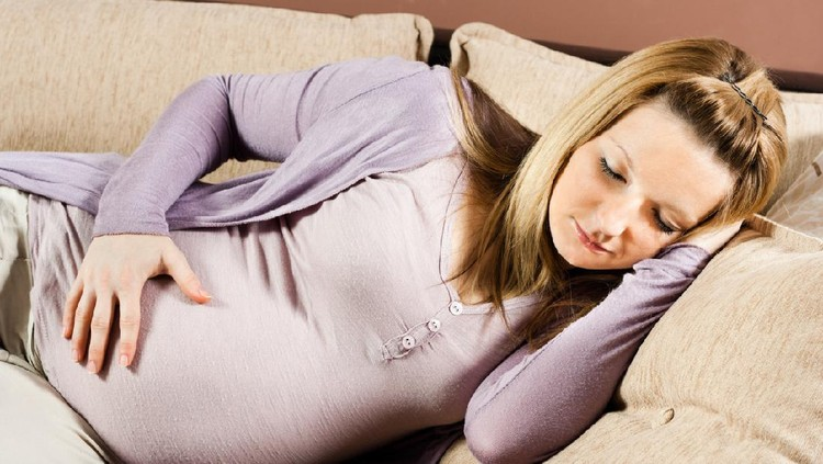 Pregnant woman is sleeping on sofa.