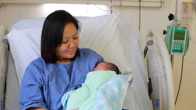 Mother holding her newborn child after labor