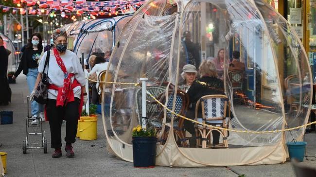 Untuk menerapkan physical distancing, sebuah kafe di New York, AS, sediakan tenda plastik tak ubahnya balon sebagai area bersantap para pelanggan.