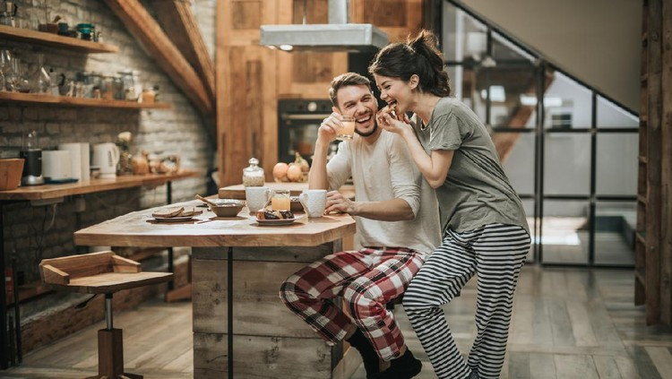 Young happy couple spending their morning together in the kitchen while woman is eating and man is drinking juice.