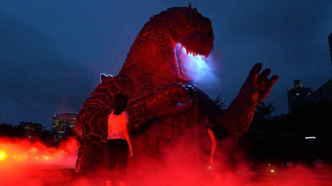 Sebuah taman hiburan di Jepang memiliki wahana flying fox yang melewati bangunan berbentuk mulut Godzilla yang sedang mangap.