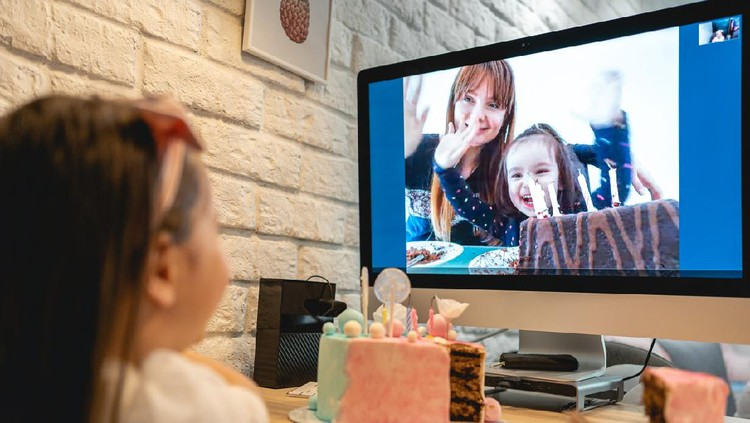 Lovely preschool age girl celebrating her 5th birthday in home isolation because of pandemic of COVID-19 in her country while talking with abroad family on a computer.