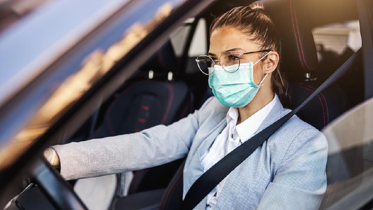 Young woman with protective mask and gloves driving a car. Infection prevention and control of epidemic. World pandemic. Stay safe.