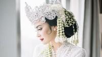 <p>Vicy Melani tampak cantik dengan siger Sunda di hari pernikahannya. Bikin pangling lho, Bunda. (Foto: Moire Photo/ Bridestory/ Dok. Instagram)</p>