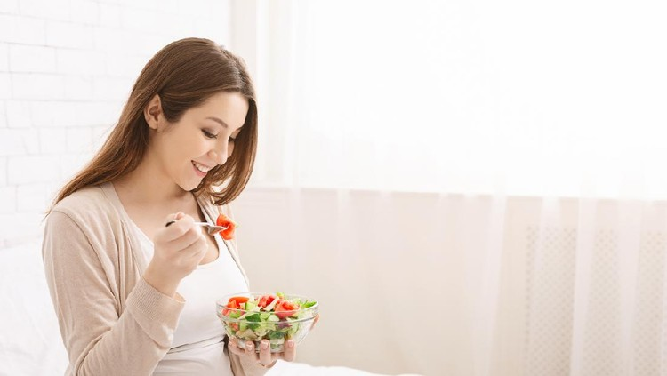 Healthy organic nutrition. Pregnant millennial woman eating natural vegetable salad in bed, empty space
