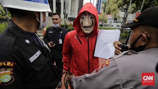 Mahasiswa bertopeng Salvador Dali melakukan aksi membakar salinan naskah Omnibus Law UU Cipta Kerja di depan Gedung MK, Selasa (27/10).