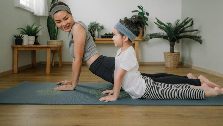 Asian little girl and her mother enjoying free time at home in the living room, practicing yoga together.