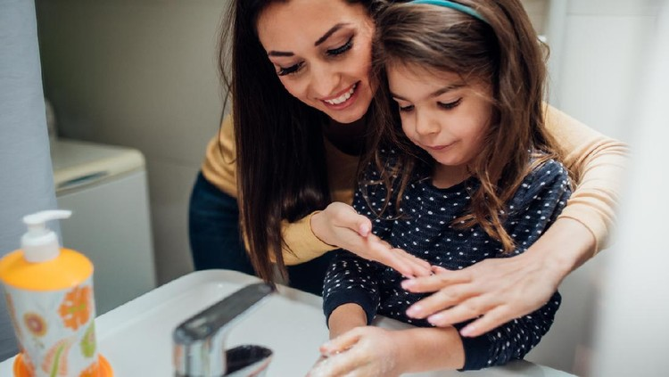 Happy woman washing hands with her daughter