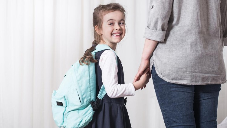 Parent and elementary school student go hand in hand on a light background . Back to school concept