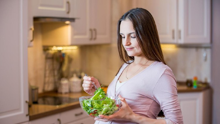 A young beautiful pregnant woman eating a fresh green salad. Healthy nutrition and pregnancy. Pregnant woman's standing in the kitchen with vegetable salad. Healthy lifestyle.