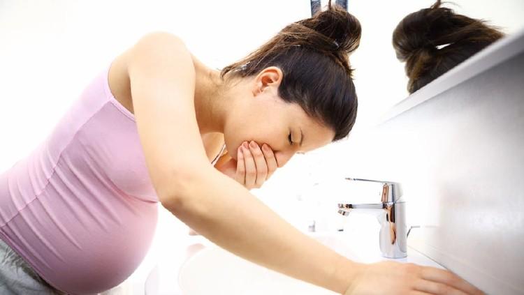 Pregnant woman in bathroom feeling sick