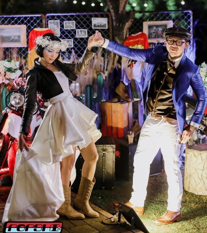 Aktris dan presenter Popi Sovia beserta suami menerapkan tema otomotif di hari pernikahan mereka. Sebab, mereka berdua memang memiliki hobi yang sama terhadap bidang otomotif, khususnya motor. Popi mendesain busana resepsi pernikahan dengan ide gaun putih pendek berekor panjang yang dipadukan dengan jaket kulit hitam serta cowgirl boots coklat. Sebagai tambahan, ia mengenakan headpiece bunga-bunga rustic. (Pernikahan Popi Sovia/Foto: Instagram/popsovia)