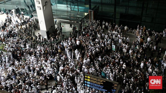 Massa yang berjalan kaki di jalan tol menuju Bandara Soetta, menggemakan takbir dan selawat menyambut kepulangan Rizieq Shihab hari ini.