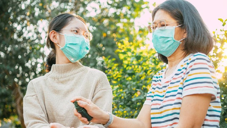 Asian people wearing protect mask and spray disinfectant alcohol on hand to prevent  spreading of the coronavirus ( Covid-19)