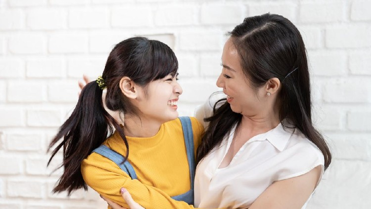 Happy Asian family Mom and teenage daughter embrace together excited, glad in a room that has sunlight from the window at home. Show Love family concept