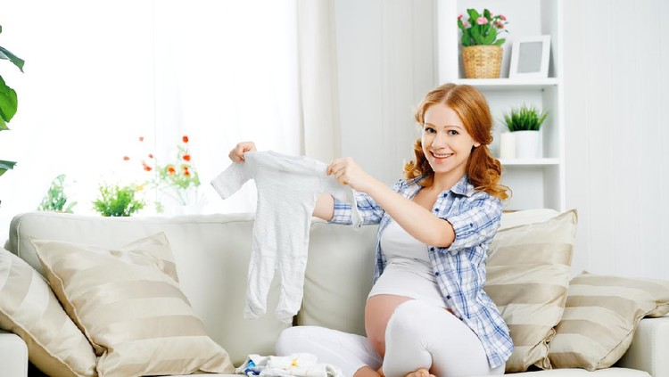 pregnant woman expectant mother prepares clothing items for the newborn baby