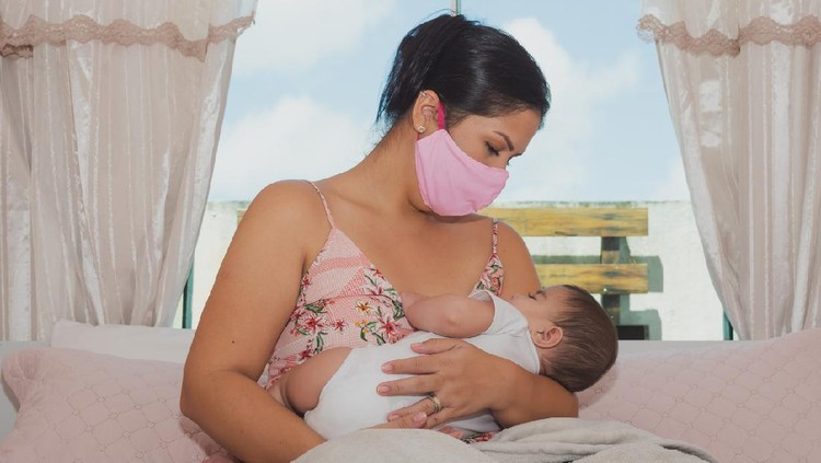Two people, mother with protective mask breastfeeding her baby son at home, they are at home do to pandemic outbreak quarantine.