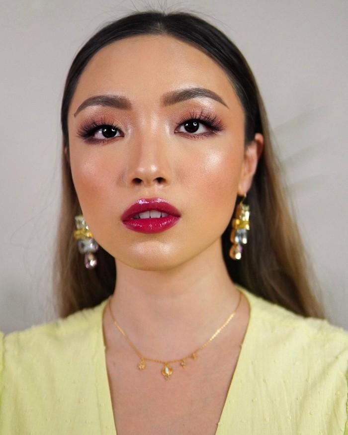 Melalui channel Youtube-nya, beauty vlogger Gel Angelica membagikan tutorial glossy makeup look yang terkesan glam dengan sentuhan lipstik merah. Untuk mendapatkan look ini, ia menggunakan glossy eyeshadow dan foundation yang dewy, serta highlighter di tulang pipi, hidung, dagu hingga inner corner. Penampilannya semakin glossy dengan sentuhan lipgloss berwarna rosy red yang juga memberi efek bibir plumpy. (Foto: instagram.com/gelangelicca)