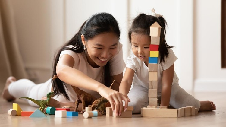 Overjoyed young Asian mom and little biracial daughter lie on warm home floor construct with building bricks together, happy millennial Vietnamese mother have fun play with small girl child