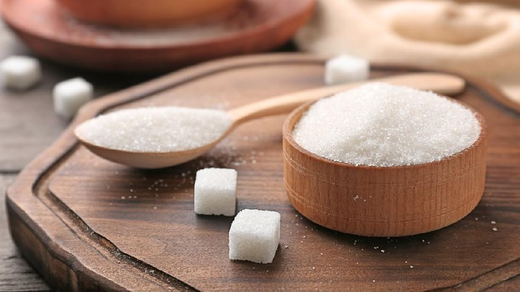 Bowl and spoon with pure sugar on wooden board