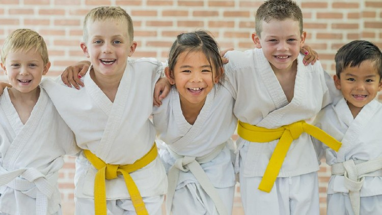 A group of elementary age children are taking a martial arts class. They are standing together in a row and are smiling while looking at the camera.