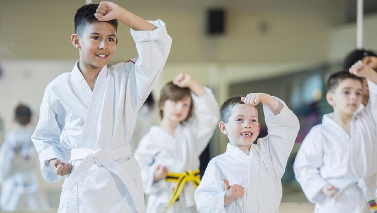 A multi-ethnic group of children are indoors at a Taekwondo academy. They are wearing martial arts clothing. They are practicing their techniques and smiling.