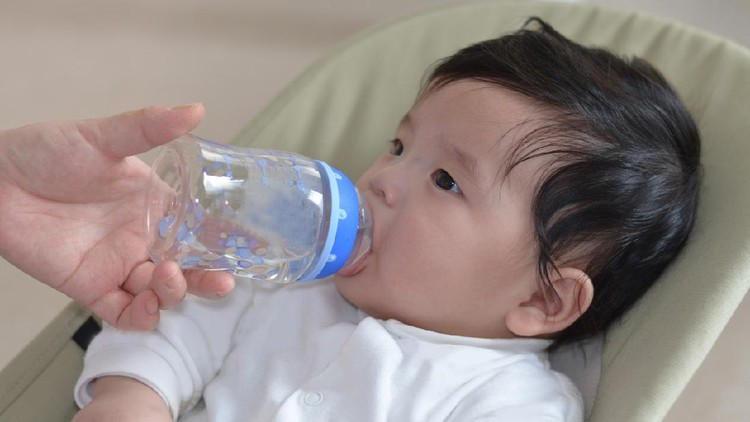 Mother give baby water from baby bottle, baby likes it