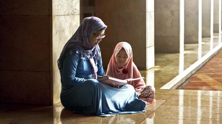 Muslim mother teach her daughter reading koran inside the mosque