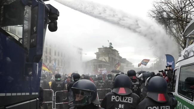 Polisi membubarkan paksa ribuan pengunjuk rasa yang menggelar aksi demo memprotes lockdown di dekat gedung parlemen Jerman pada Rabu (18/11).