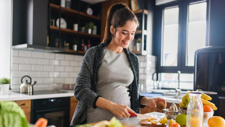 Young beautiful pregnant woman preparing healthy meal with fruites and vegetables