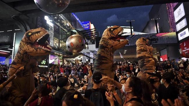 Demonstran kenakan kostum dinosaurus saat aksi protes pro-demokrasi di Thailand, Sabtu (21/11).