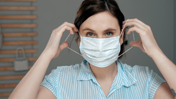 Attractive girl puts on surgical mask on her face. Cold, flu, virus, acute respiratory infections, quarantine, epidemic, irony, sarcasm concept. Close up view