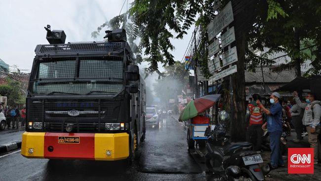 Polisi melakukan penyemprotan disinfektan di wilayah Petamburan, Jakarta Pusat, yang juga merupakan markas Front Pembela Islam (FPI) pada Minggu (22/11).