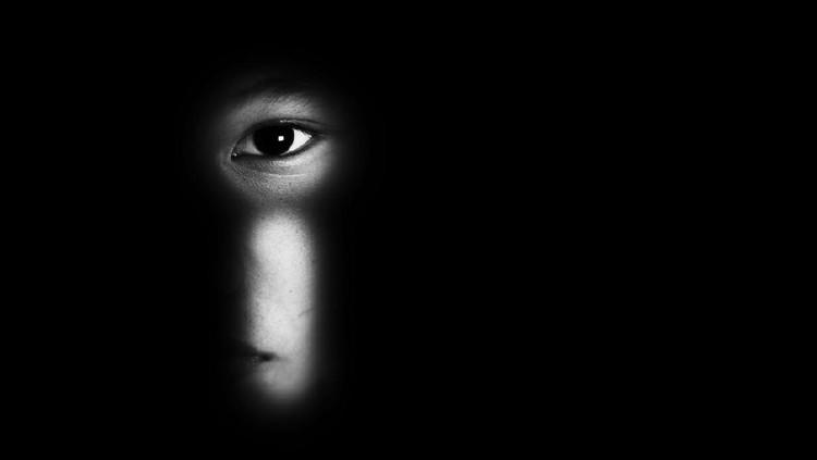 eye of boy through key whole, child abuse concept