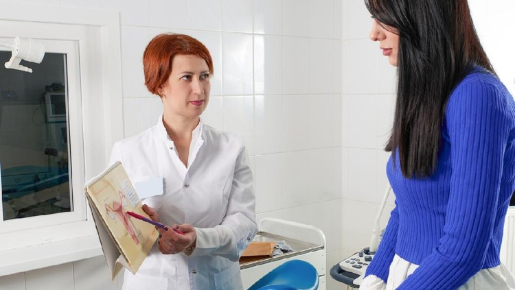 Gynecologist showing a picture with uterus to a young woman patient, explaining the features of women's health