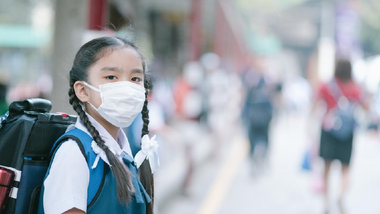 School Girl wearing mouth mask against air smog pollution in Bangkok city, Thailand