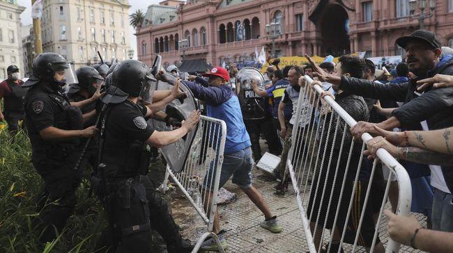 Kericuhan terjadi antara ratusan fan Diego Maradona dengan polisi di luar Istana Presiden Argentina. Ratusan fan berebut melihat peti mati Maradona.