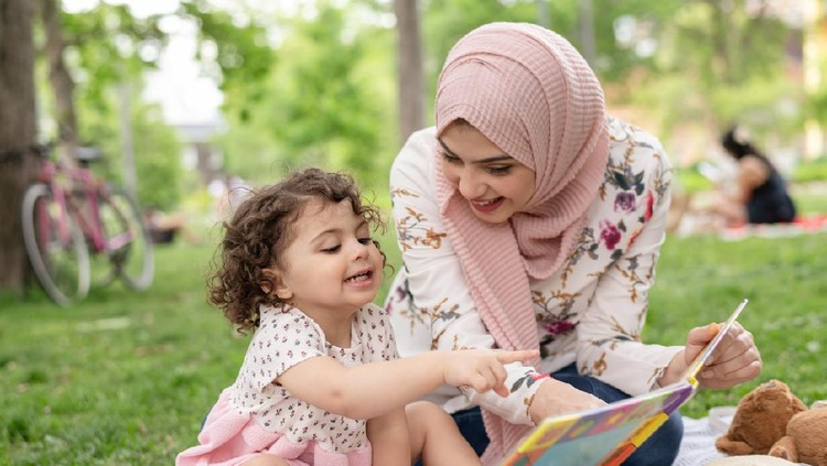 A young Arab American mother reads with her young daughter in a public park. She is wearing a hijab and having a great time as they turn pages and point to pictures together.