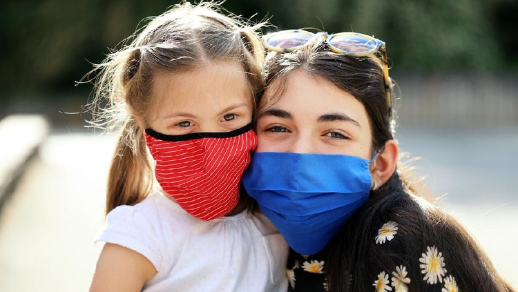 Two cheerful girls wearing face protective mask having fun outdoors