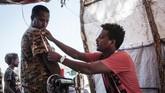 Seorang penjahit Omar Ibrahim yang melarikan diri dari konflik Tigray membantu sesama pengungsi membuatkan baju baru dan memperbaiki lubang di baju lama mereka.