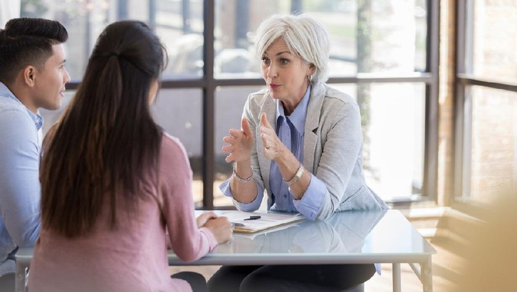Serious Caucasian senior female counselor gestures while giving important advice to a young married couple.