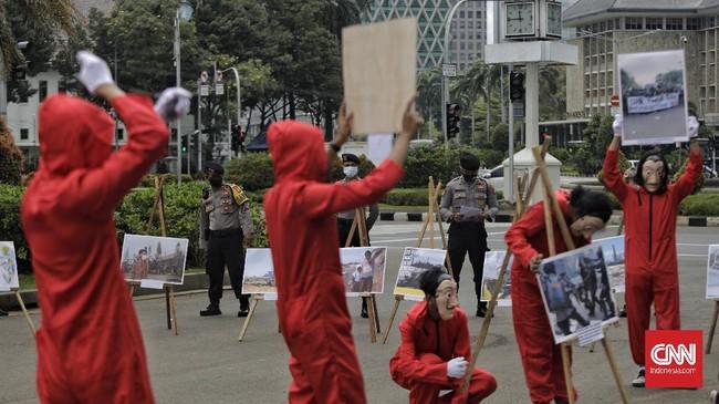 Sejumlah aktivis #BersihkanIndonesia berkostum merah bertopeng Salvador Dali melakukan aksi di Monas mengajak masyarakat melakukan pembersihan kebijakan korup.