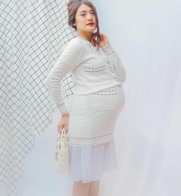 Tak ada halangan bagi Anissa Aziza untuk menggunakan desain pakaian apapun selama hamil besar. Seperti potret di atas ini, Anissa terihat cocok mengenakan skirt suit warna putih tulang dengan aksen emboss dan garis putus-putus serta hand bag berwarna krem. Lalu, ia mengakali bagian rok yang terlalu mengangkat karena ada baby bump dengan pleated skirt warna senada. Sangat menginspirasi para bumil, ya. (Foto: Anissa Aziza/Foto: Instagram/anissaaziza)