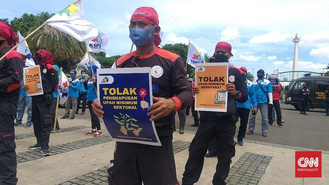 Polisi memasang kawat berduri untuk menghalangi para buruh yang hendak berdemo menolak Omnibus Law di depan gedung MK.
