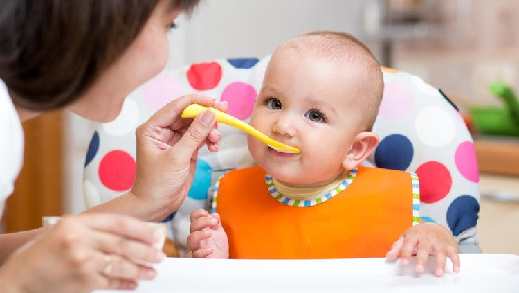 smiling baby girl eating food with mom on kitchen