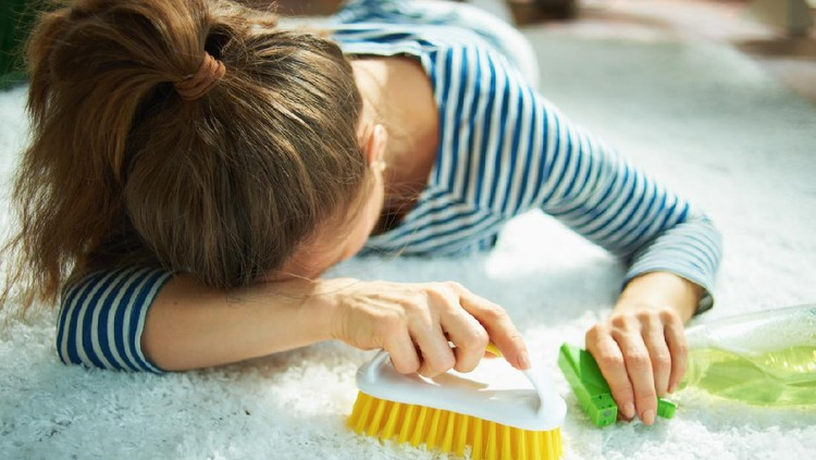 Closeup on tired woman in striped t-shirt and white pants with spray bottle of green cleaning supplies and yellow brush laying on white carpet at home in sunny day.