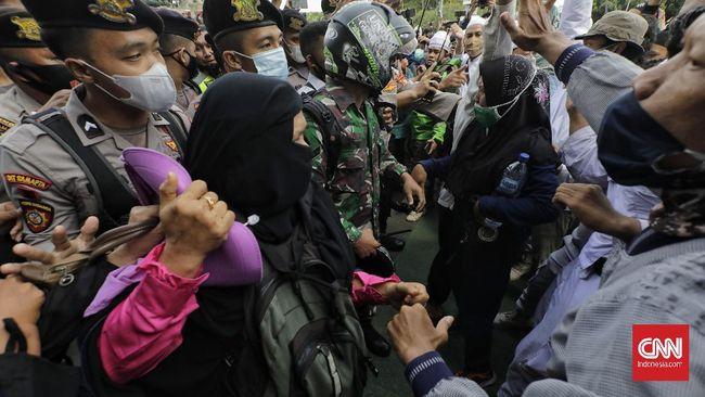 Sejumlah orang yang bagian dari massa Aksi 1812, termasuk kaum ibu, masih mencoba bertahan saat polisi berupaya membubarkan mereka.